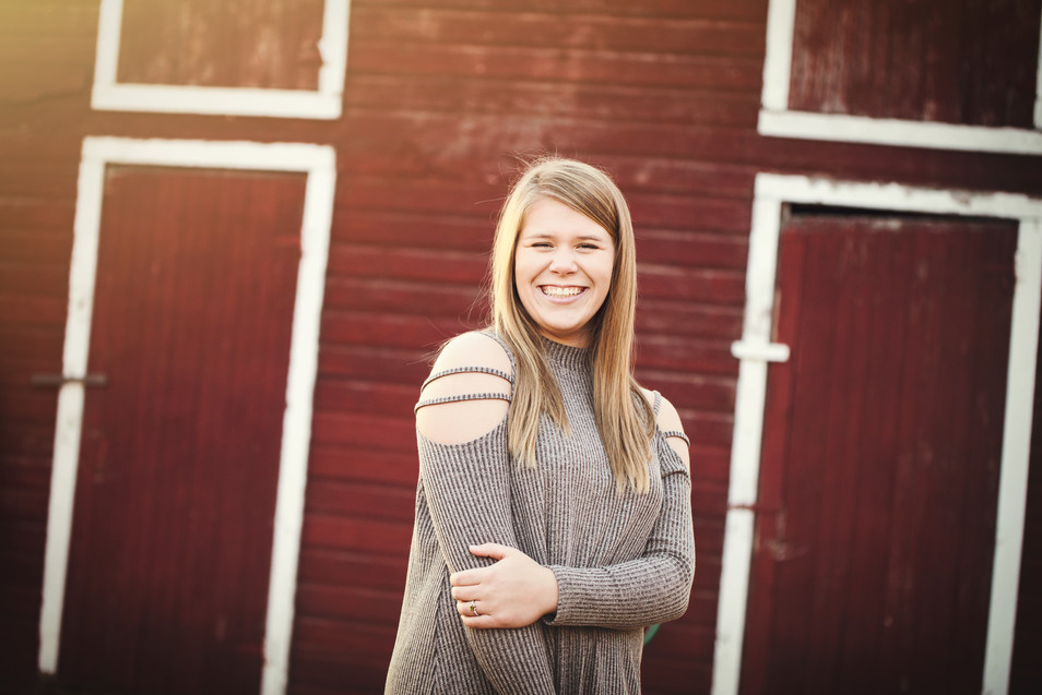 senior girl in front of red barn
