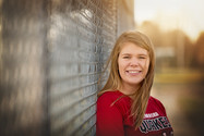 senior girl against softball fence