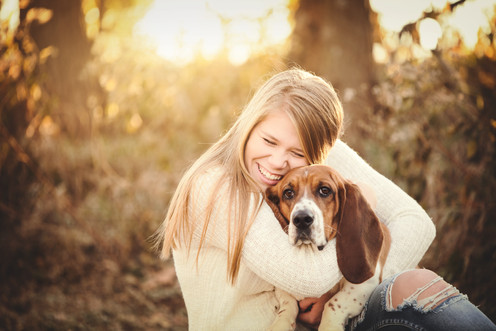 senior girl with basset hound in the woo