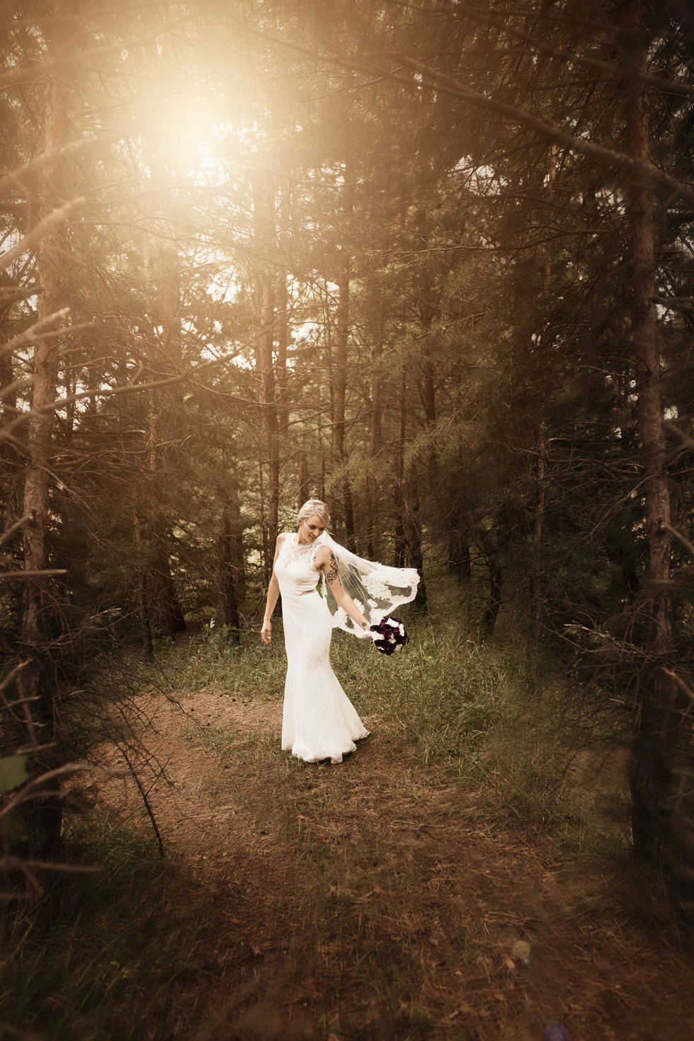 Bride in the woods with flowing veil