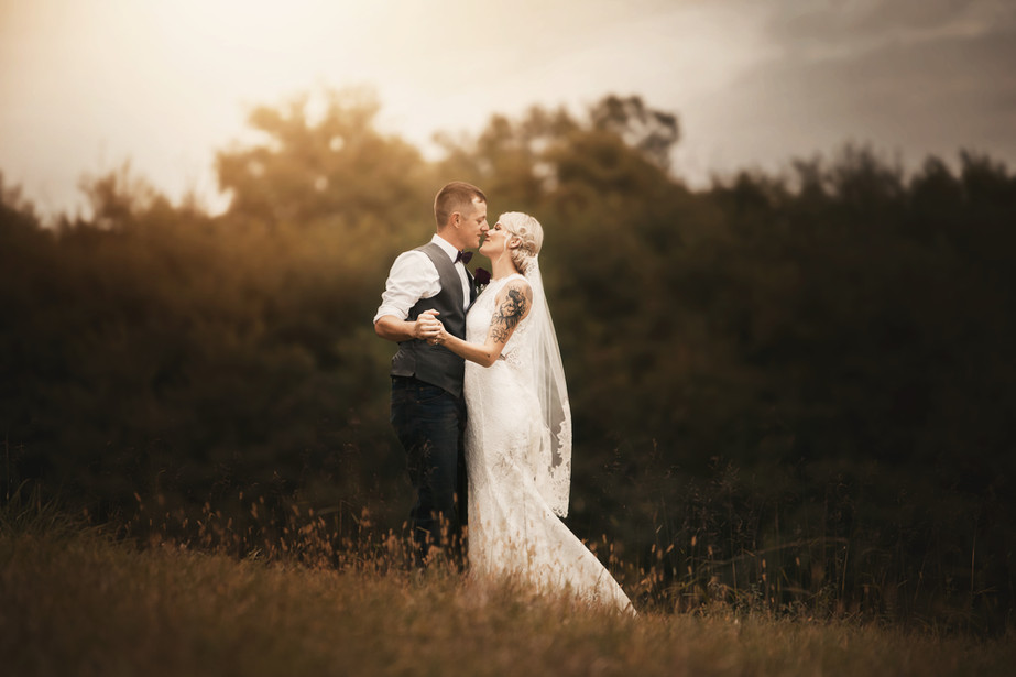 bride and groom on a hill kissing