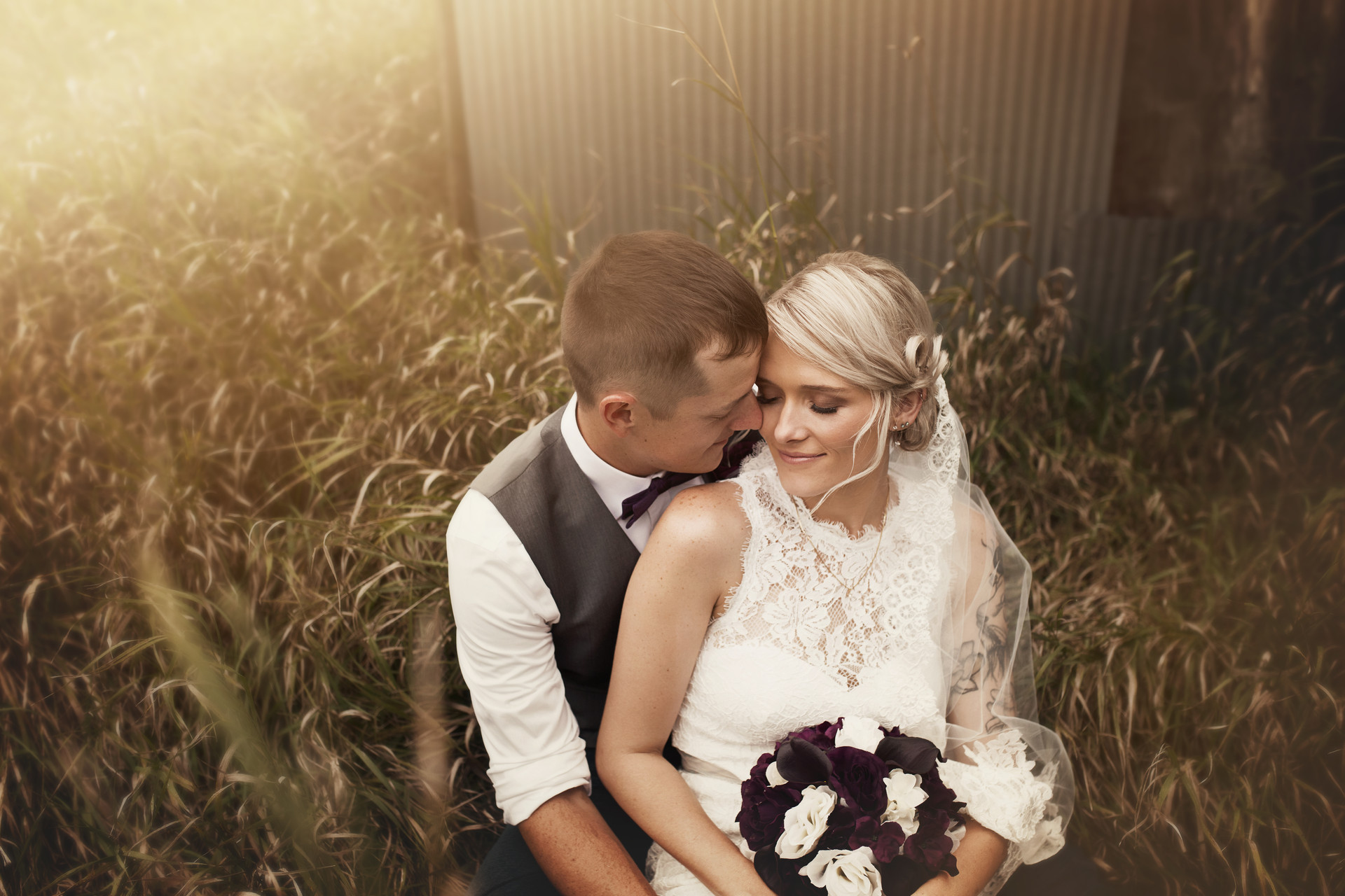 Bride and groom cuddling in overgrowth