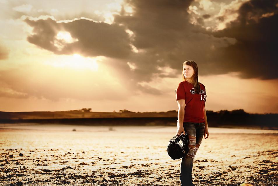 senior girl softball player in field