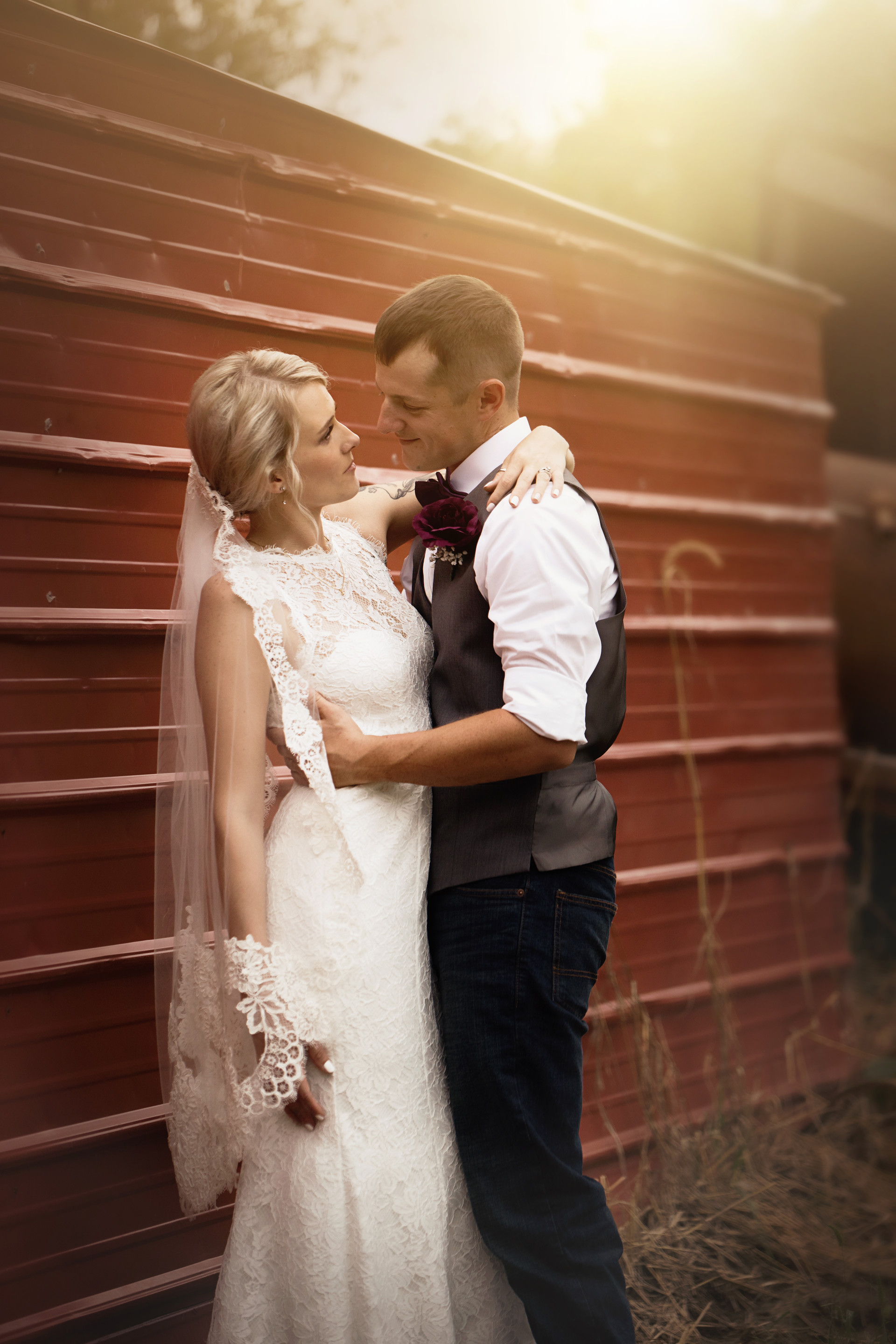 Bride and groom against red barn