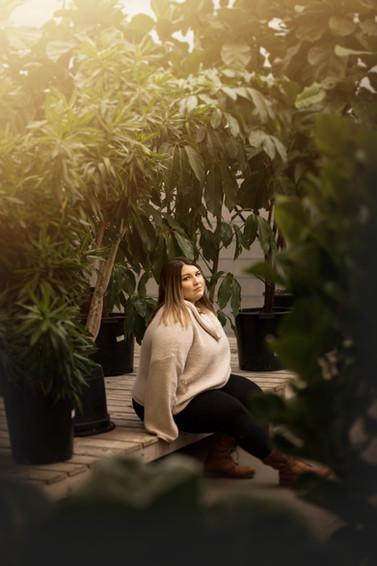 Senior girl sitting in greenhouse