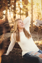 senior girl in the woods laughing