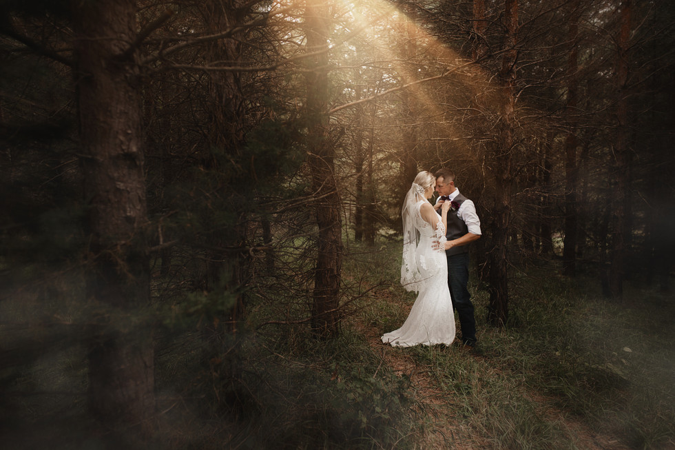 Bride and groom in the woods with lightf