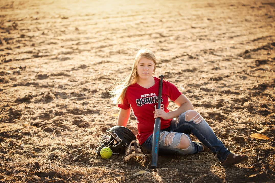senior girl in field with softball glove