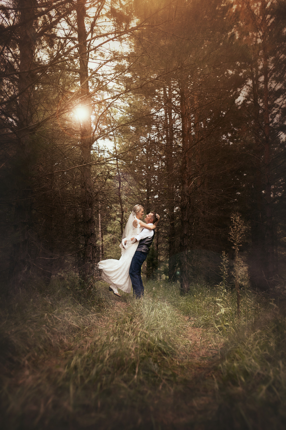 Bride and groom in the woods with light