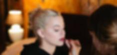 Asthildur makeup artist puts on lipstick.