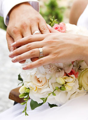Hands and rings on wedding bouquet.jpg