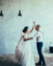 Cute wedding couple dancing at loft inte