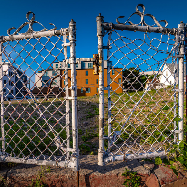 Gate guarding an empty lot. Must have been a house there at one point.