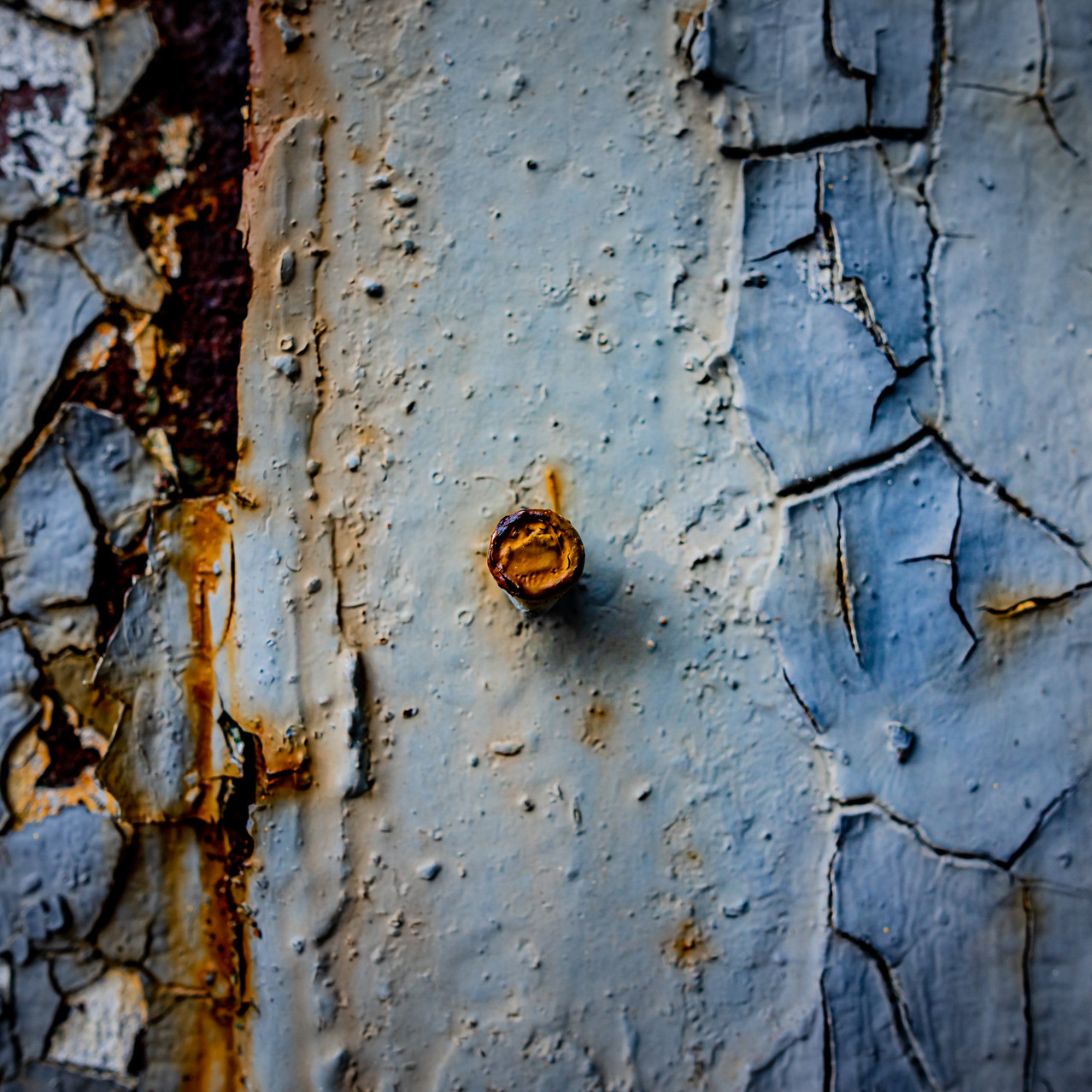 Old nail and peeling cracked paint.