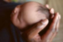 Black daddy holding newborn baby's head