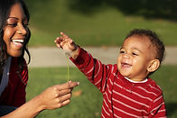 Mother and son playing with a dandelion