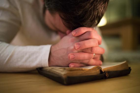 Unrecognizable man praying, kneeling on