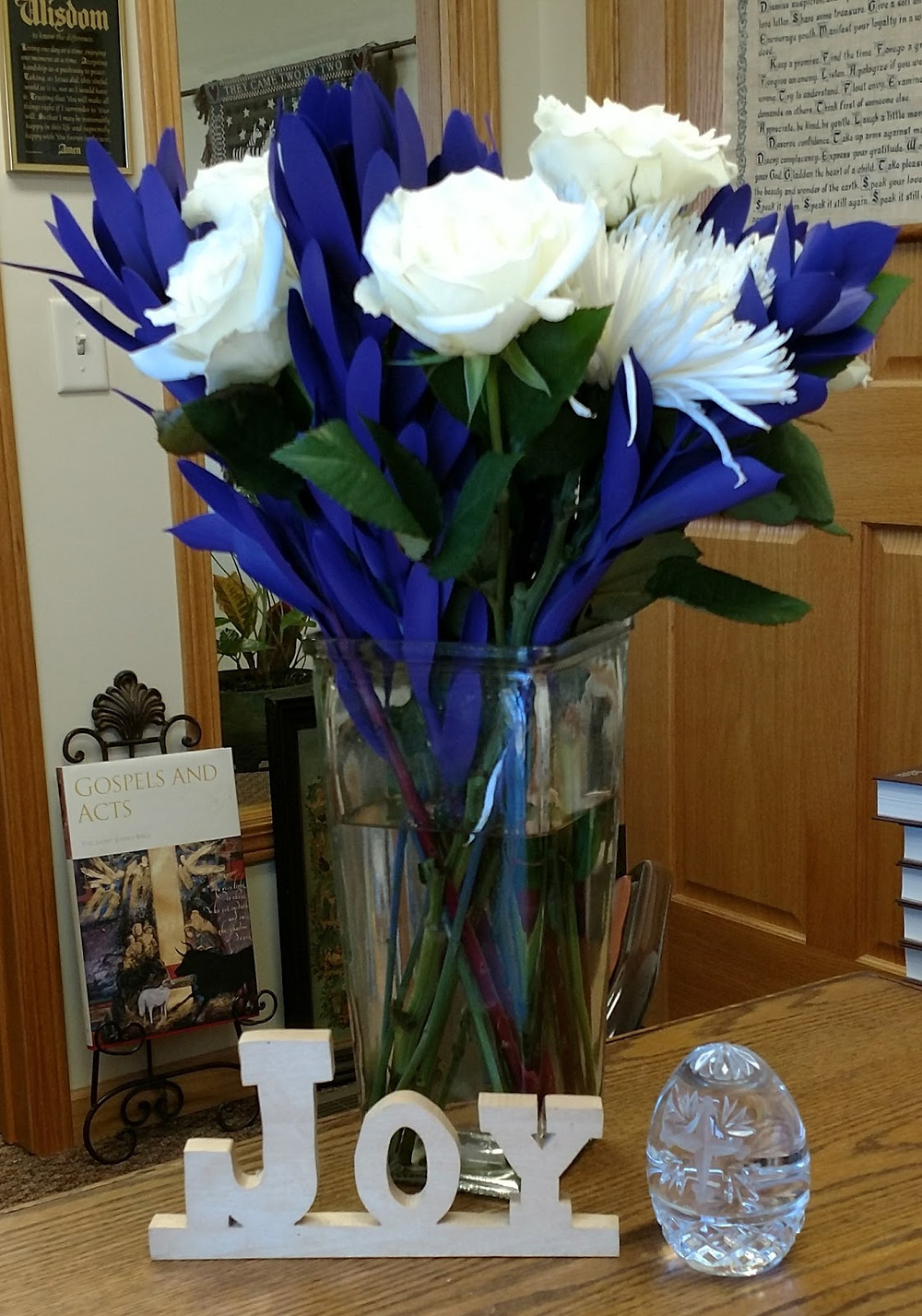 """white and purple flowers in glass vase, wood-carved """"joy"""", crystal egg"""