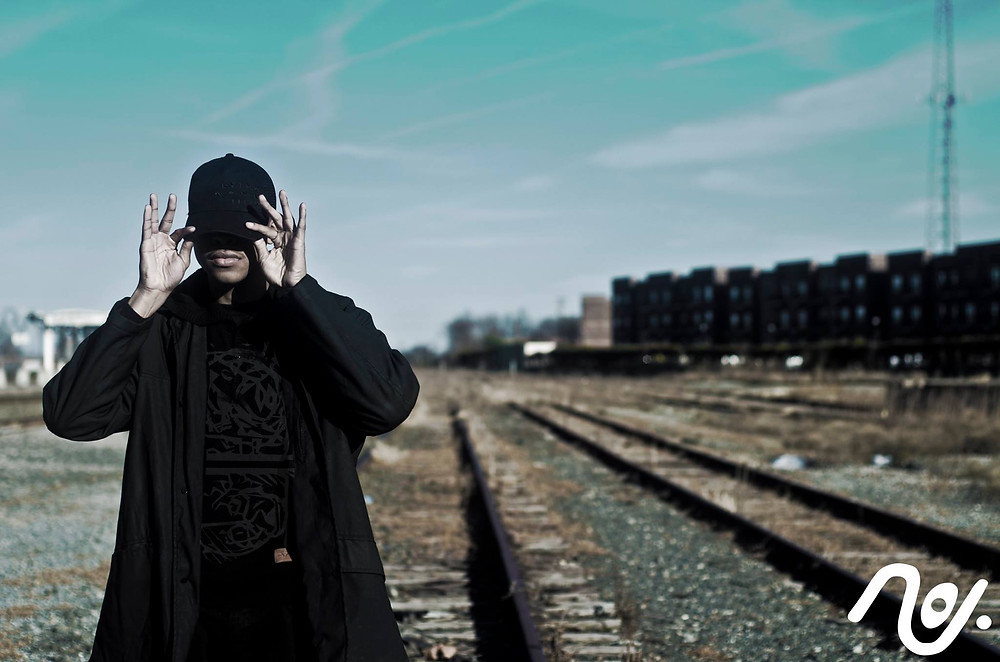 Denzel Fleming is standing posed like Jay-Z with his index fingers and thumbs clutching the brim of his black baseball cap. He is wearing all black. A black raincoat, hoody and graphic tee. The environment is an out of service railroad track, apartment complex in the background and a turquoise open sky.