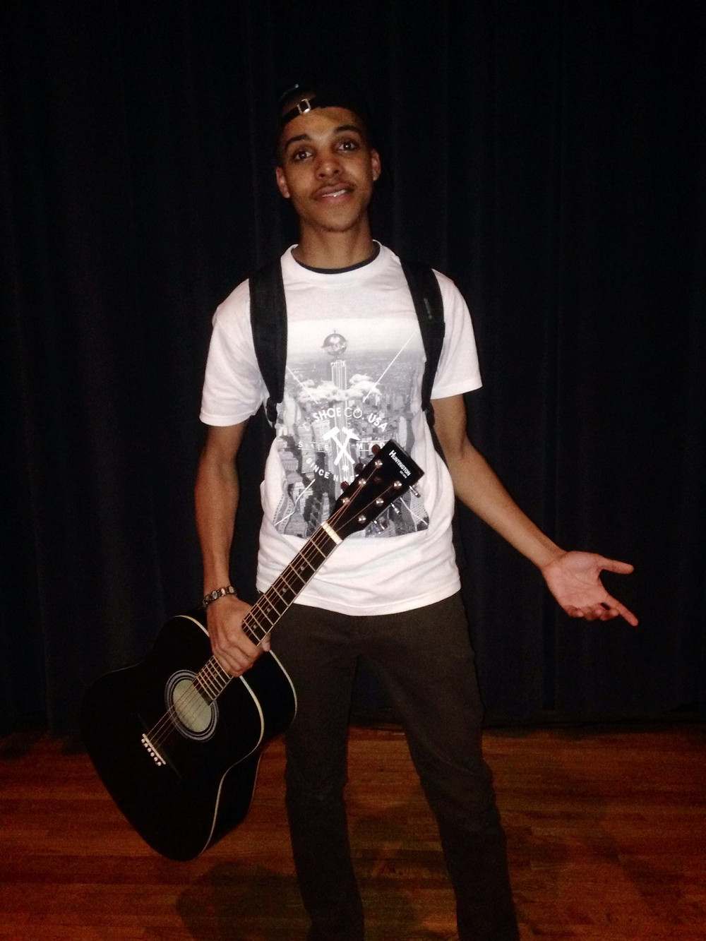 Denzel Fleming is pictured standing with a guitar in his right hand. His left hand is open toward the sky with his index finger and thumb relaxed in a nonchalant manner. He is wearing a white graphic tee, brown pants, a black backpack and hat.