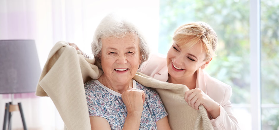 Caregiver covering senior woman with pla