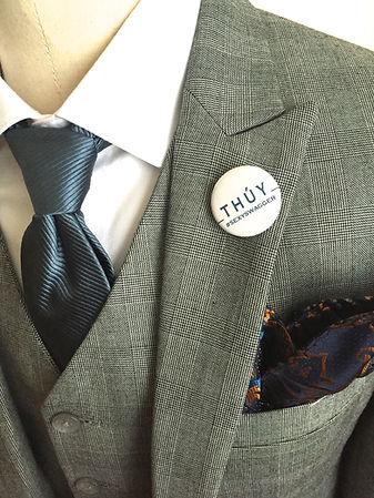 Close-up of 3-piece light gray suit, peak lapel, vest, and blue tie with white shirt.