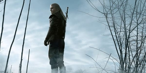 Geralt of Rivia standing in a winter forest as he ponders his next move.