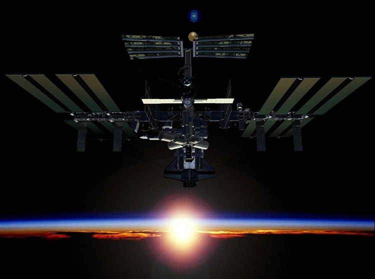 The International Space Station hovers over Earth during sunrise.