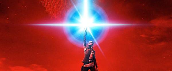 Rey raising her lightsaber toward the sky.
