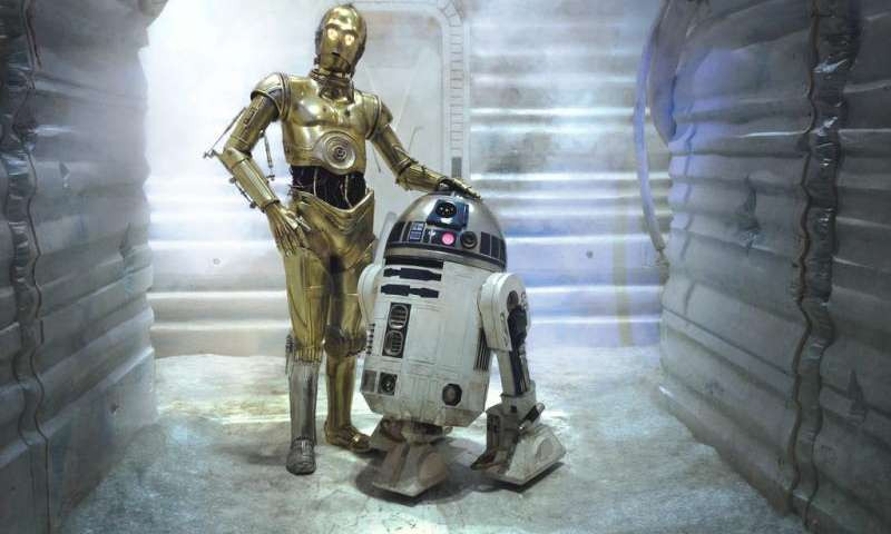 R2-D2 and C-3PO posing in a narrow hallway.