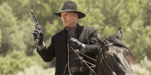 The Man In Black aims his revolver while riding on horseback.
