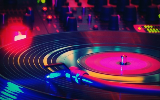 A vinyl record spins under colorful lights.