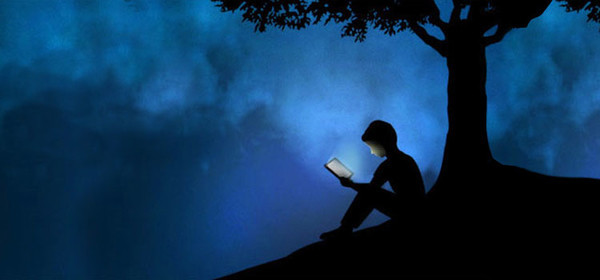 A young boy reading an eBook under a tree.