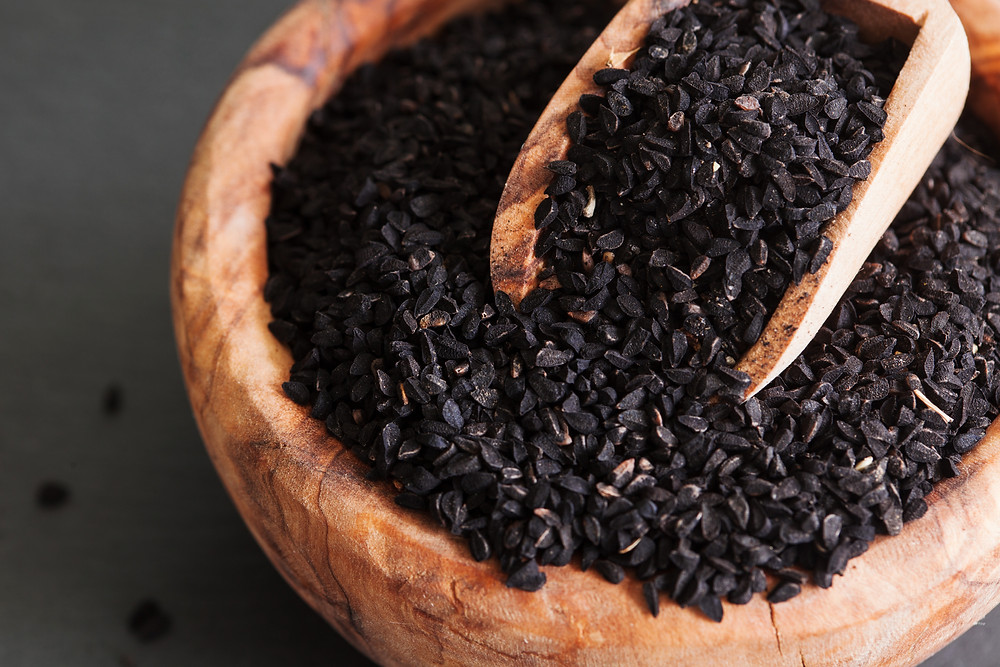 a wooden container and small wooden shovel filled with Nigella Sativa black seeds