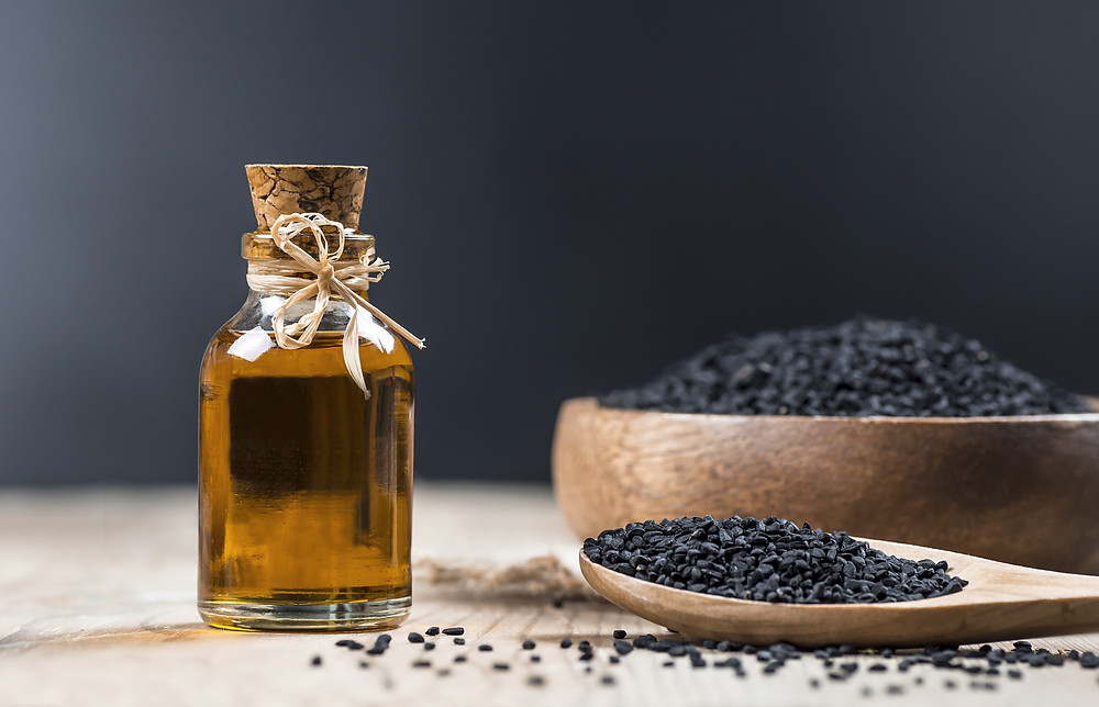 a pciture of Nigella Sativa black seed as well as black seed oil in a apothocary jar that is corked closed  brown wooden spoon and some in s brown wooden bolw