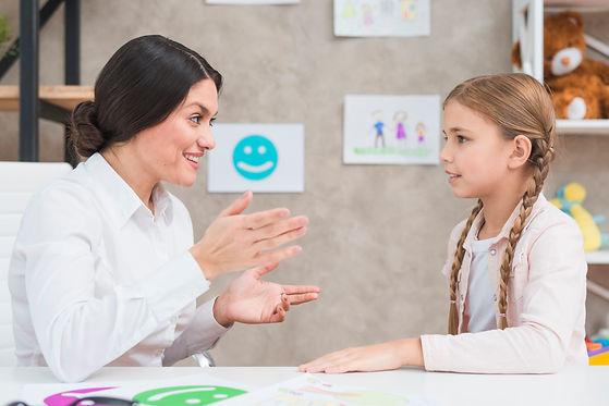 smiling-portrait-girl-female-psychologist-having-conversation-office.jpg