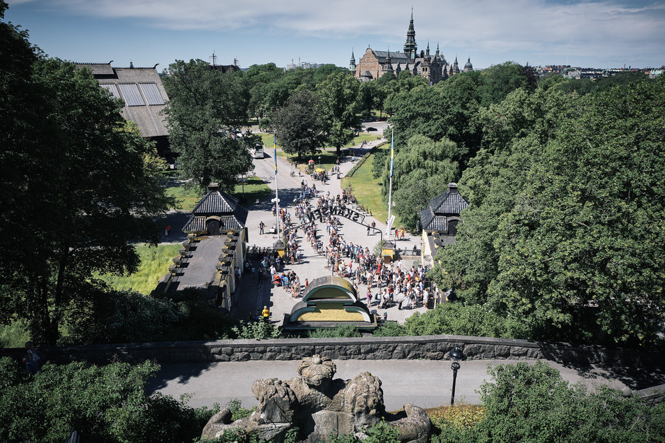 SWEDEN / Stockholm / 21.06.2019 / People are queuing at the entrance  to Skansen, the world`s oldest open air museum, to attend the Midsommar festivities there. The Vasa Museum in the background. © Gregor Kallina