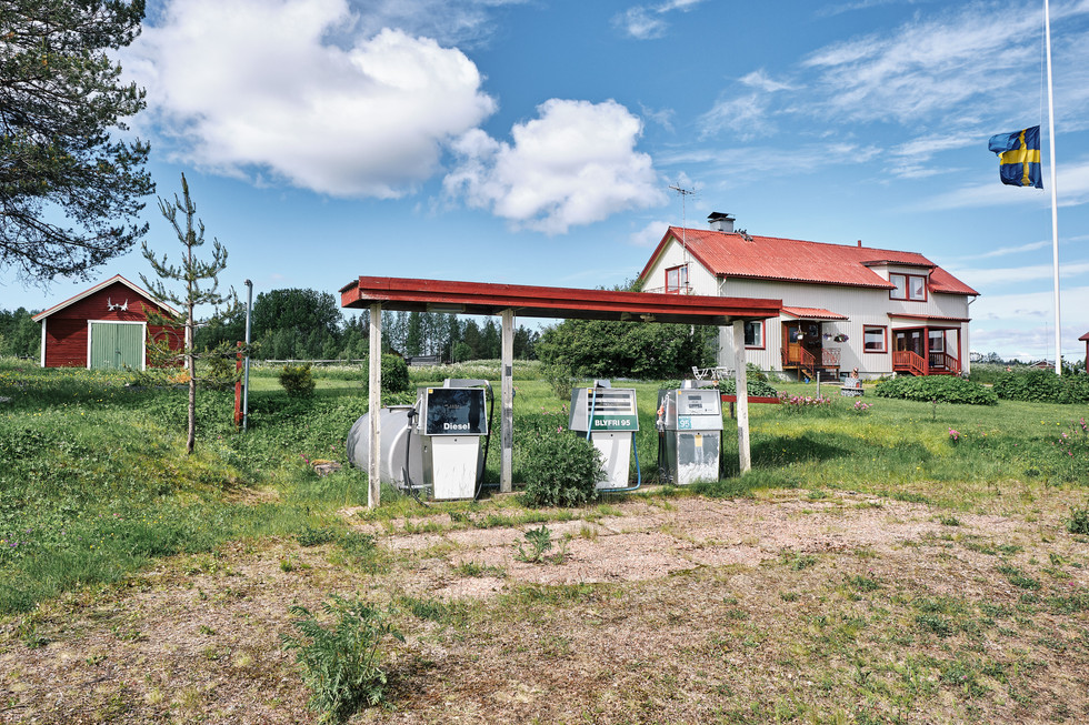 """SWEDEN / Lainio / 27.06.2019 /  Petrol station in Lainio, parish of Vittangi. The Swedish flag is on half mast due to a funeral taking place in the village. From my project """"Awakening"""". © Gregor Kallina"""