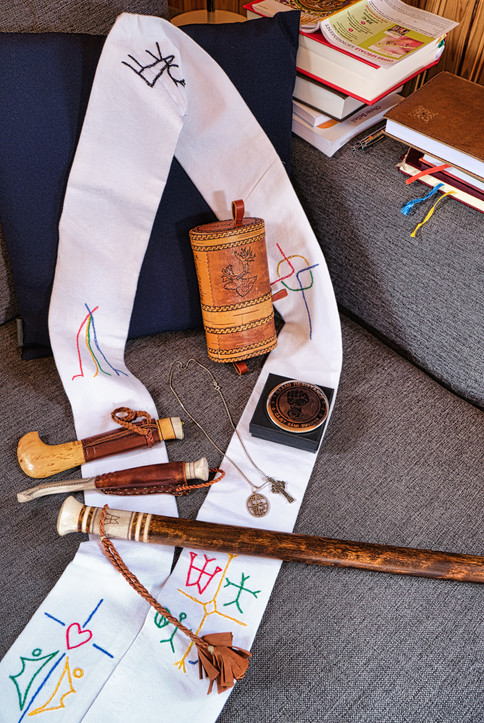 """SWEDEN / Vittangi / 24.06.2019 / At home of Jean-Claude Marclay, a Swiss-born priest who is responsible for the parish of Vittangi in Nothern Sweden. The picture shows his most important belongings: His first knife of the Sami people, received from his best friend, a knife from a Sami priest for his birthday in Kurravaara 2017, walking staff made by artist Lars Levi Sunna, coffee and sugar bowl, Sami pin of resistance, celtic cross and trolltrumma, self-embroidered stole with Christian and Sami symbols. From my project """"Awakening"""" © Gregor Kallina"""