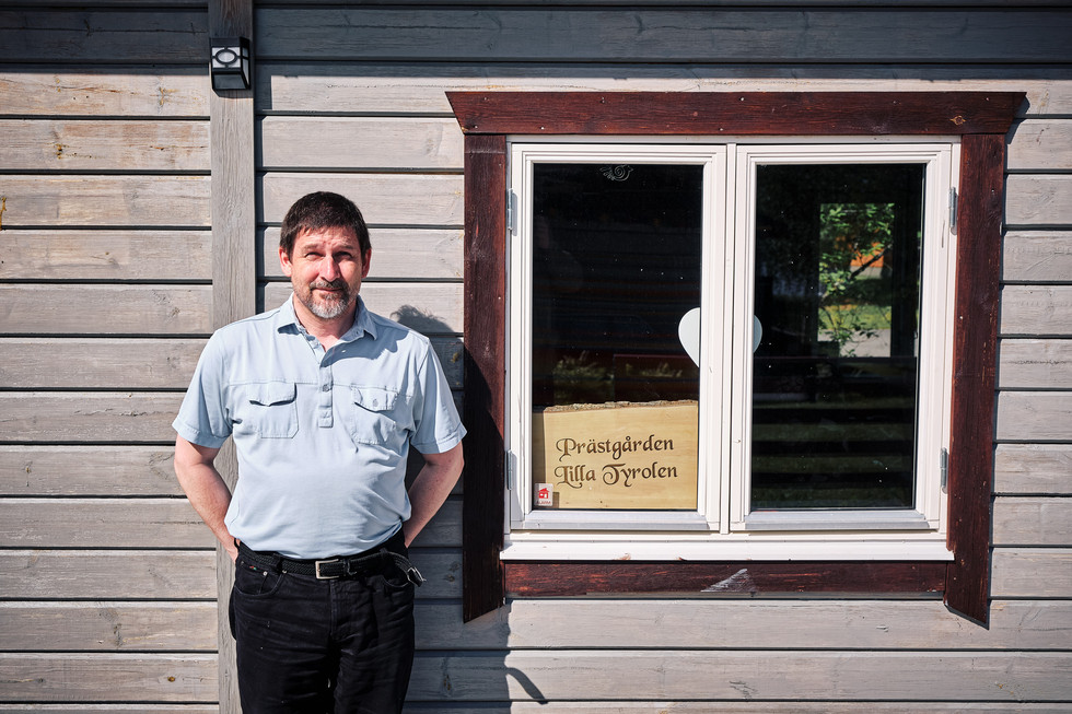 """SWEDEN / Vittangi / 24.06.2019 / Swiss-born priest Jean-Claude Marclay is standing in front of his home, what he calls """"Rectory Little Tyrol"""", with reference to his 16 years spent in Innsbruck. He is responsible for the parish of Vittangi, 1500 members on 6000 square kilometres in the very north of Sweden. Besides representing the word of god he also has his own opinion on environmental issues in the area. From my project """"Awakening"""". © Gregor Kallina"""