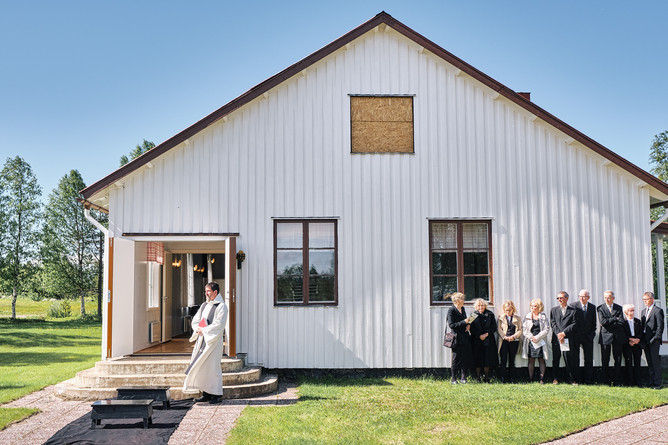 """SWEDEN / Lainio / 27.06.2019 / Swiss-born priest Jean-Claude Marclay is waiting for the coffin to arrive at a funeral in the village of Lainio. He is responsible for the parish of Vittangi, 1500 members on 6000 square kilometres in the very north of Sweden. Besides representing the word of god he also has his own opinion on environmental issues in the area. From my project """"Awakening"""". © Gregor Kallina"""