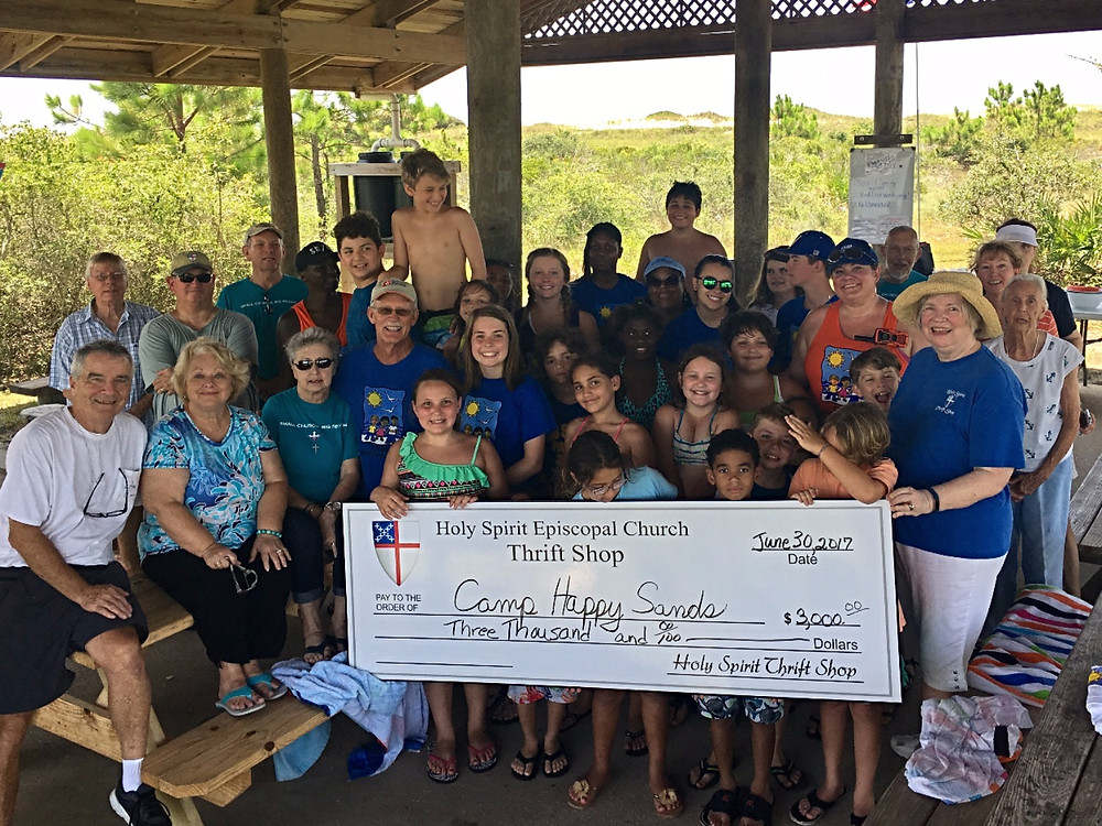 Millie Ericson, Thrift Shop Board chair and members of Holy Spirit Church present check to Charlie Roose and the staff and children of Camp Happy Sands