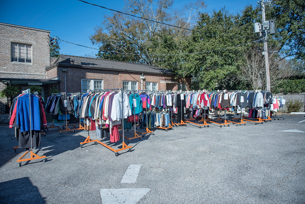 Racks filled with clothing in the parking lot at Trinity-Mobile waiting to be delivered to the Mobile fairground for Project Homeless Connect. In addition, boxes filled with socks, underwear, scarves, hats and other items that could not be hung on the racks were loaded in an SUV and on a trailer. (Photo by Bob Peck)