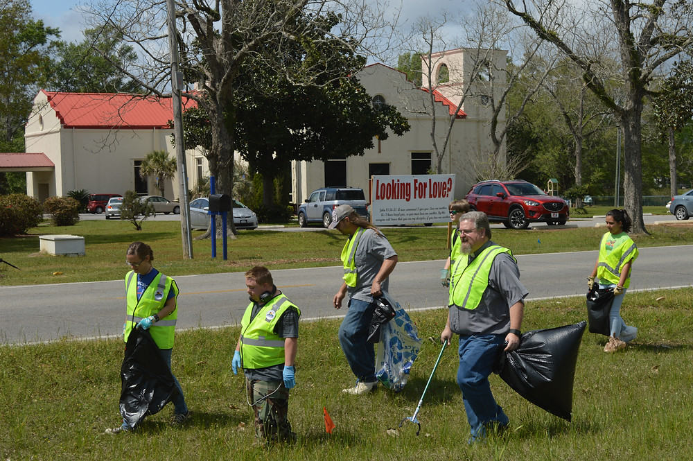 Members of St. Monica's, Cantonment, jooin together to beautify highway in their neighborhood. Photo by Viven Welch
