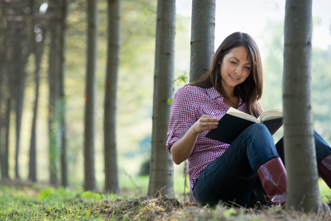 a-woman-sitting-reading-a-book-under-the