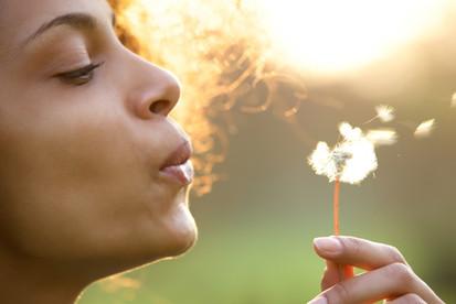 beautiful-young-woman-blowing-dandelion-