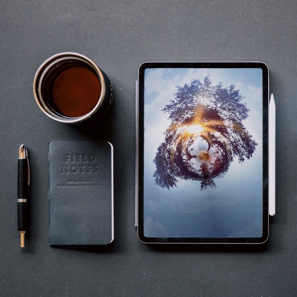 Lay flat image of iPad Pro with notebook, pen and cup of coffee