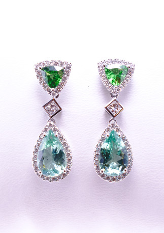 3.74 carat total weight of teal tourmaline set in 18k white gold with 1.17 carat total weight of tsavorite garnet and .94 carat of princess cut and round brilliant diamonds