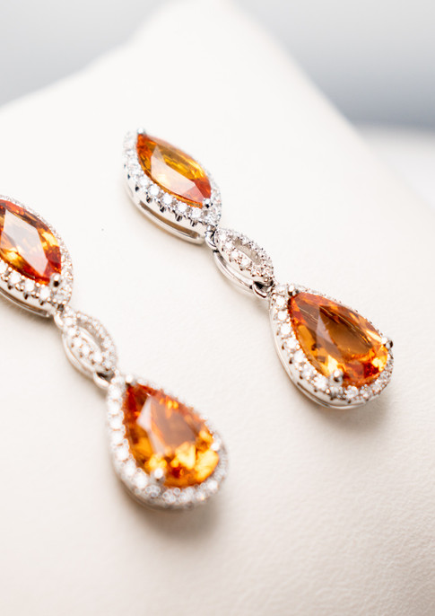 3.32 carat total weight of spessartite garnet and 1.64 total weight of orange sapphire set in18k white gold, with .57 carat total weight of round brilliant diamonds