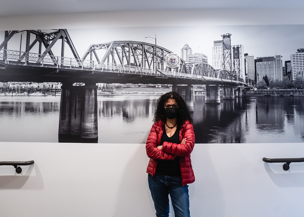 (Apr 2020) Melissa Toledo in front of her photograph of the Portland's Hawthorne Bridge. Astikos Lofts, Tigard, OR.